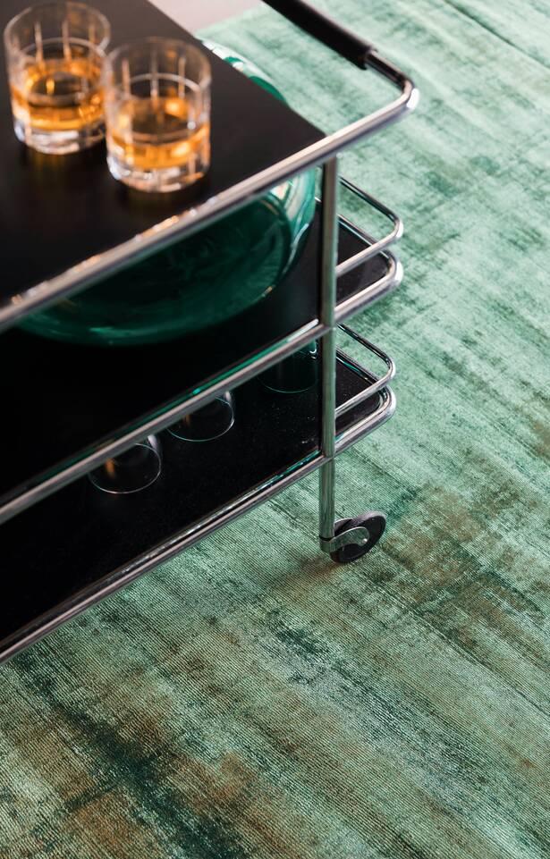 Tapete handloom tip share  em verde, numa canto de leitura.